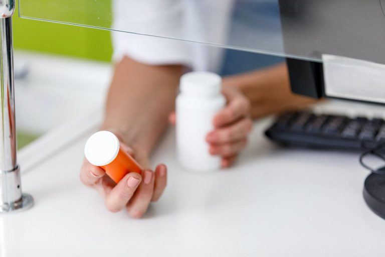 cropped shot of pharmacist holding containers with medication