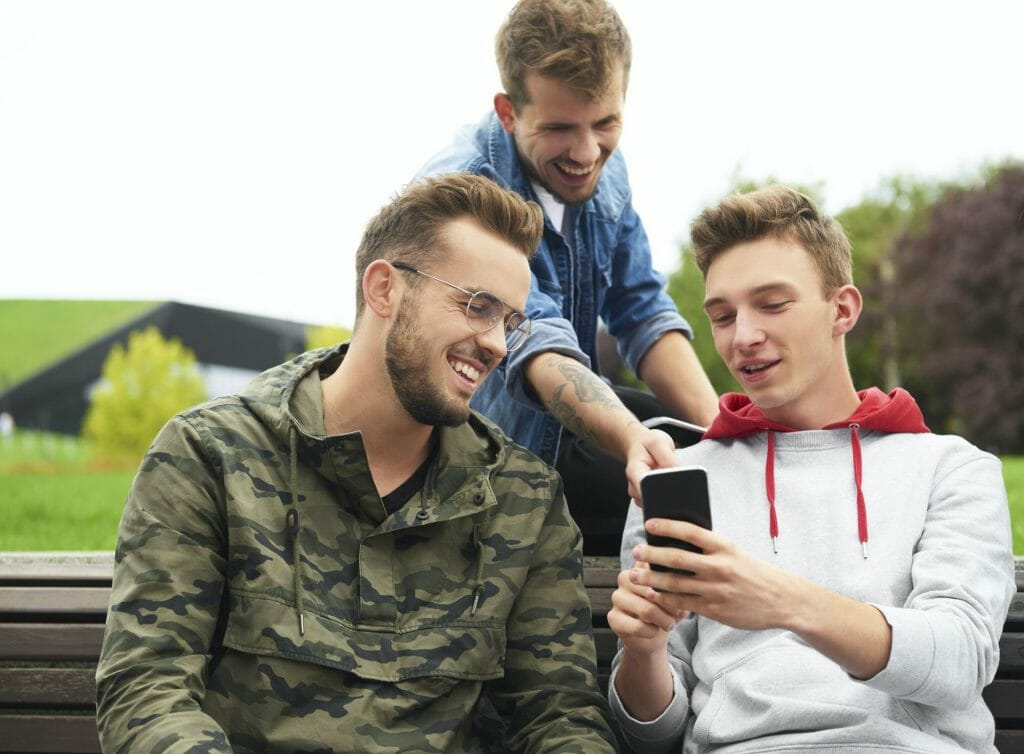 Happy men looking at smart phone and sitting on bench