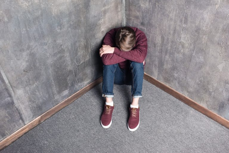 High angle view of depressed teenage boy sitting on floor