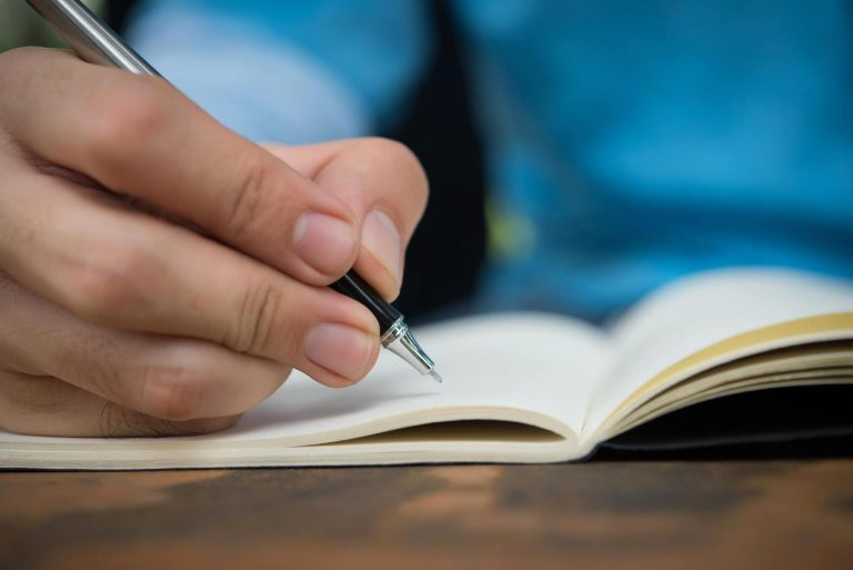 Man Hand write on the notebook.