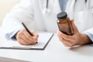 Medical doctor writing prescription for patient about pills