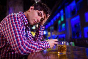 Portrait of sad man at bar counter