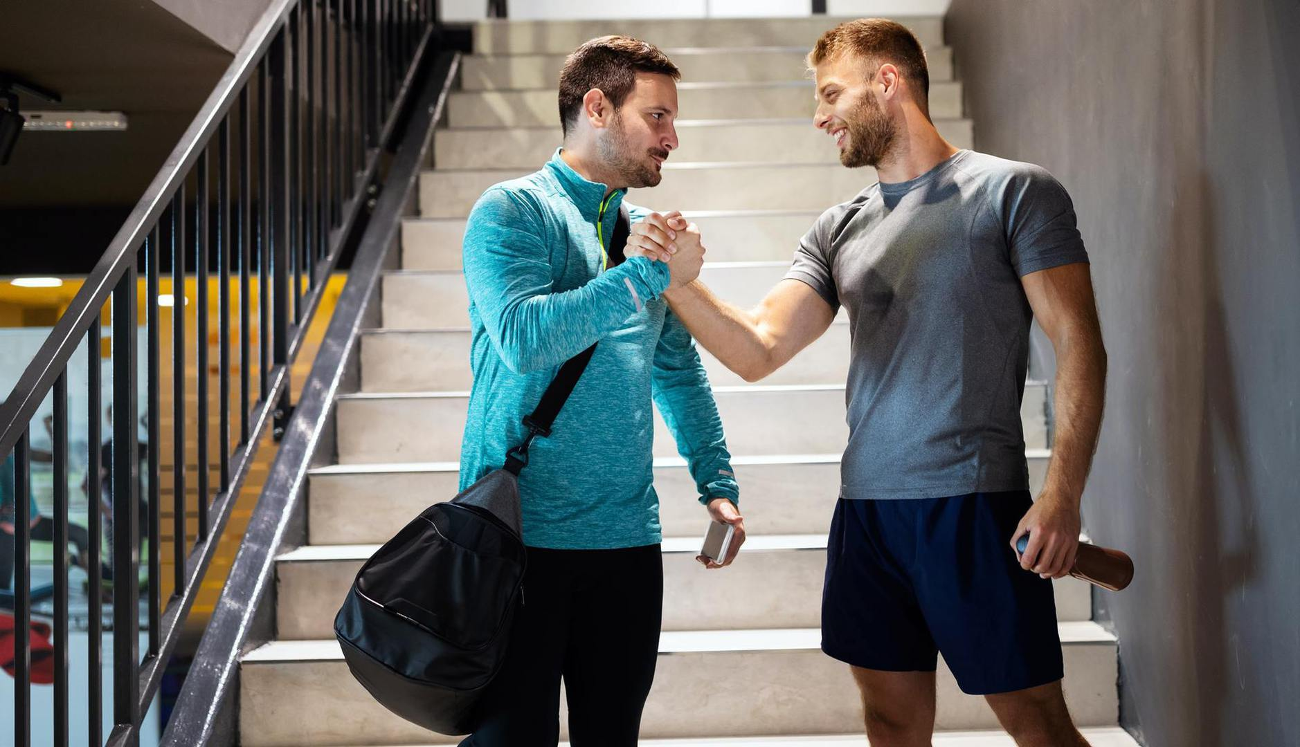 Sport, fitness, healthy lifestyle and people concept. Happy fit friends men talking after workout