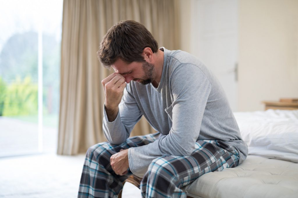 Stressed man sitting on the bed