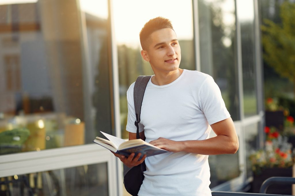 Student in a university campus with a books