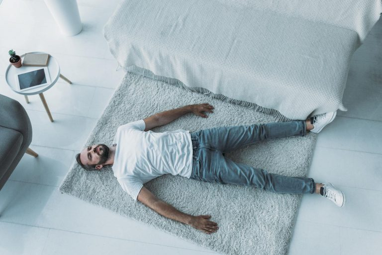 top view of sad bearded middle aged man with depression lying on carpet at home