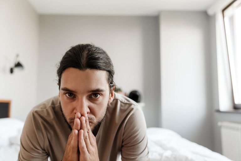 Young man in depression sitting on bed