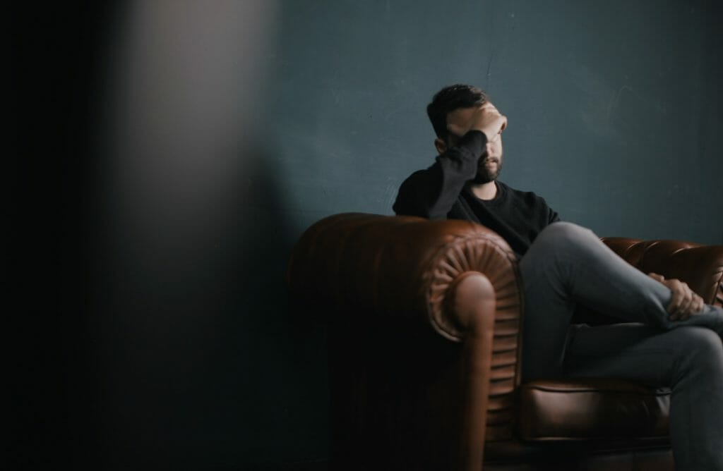 a man holds his head while sitting on a sofa
